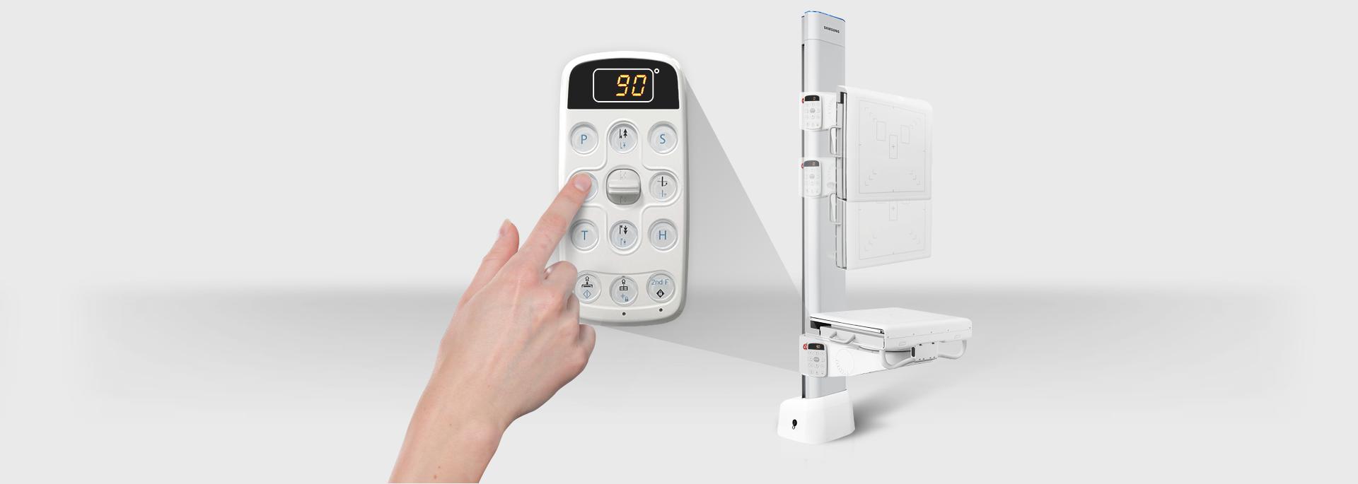 Im Vordergrund zeigt ein Finger auf das Bedienpanel, im Hintergrund sieht man das Stativ des digitalen Röntgensystems GC85A von Samsung.
